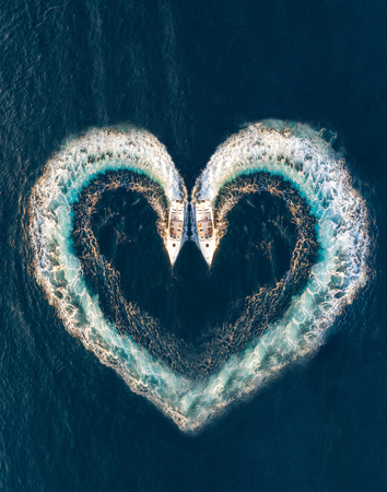 Photo pour Two boats form a shape of a heart on the ocean surface; aerial top down view - image libre de droit