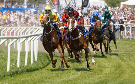 Photo pour STOCKHOLM, SWEDEN - JUNE 06, 2019: Closeup of tough fight between many jockeys riding arabian race horses and audience in the background at ATG Nationaldags Galoppen at Gardet. June 6, 2019 in Stockholm, Sweden - image libre de droit