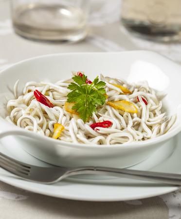 Foto de Baby eels or elver substitute in garlic sauce, a traditional Spanish tapa. Gulas al ajillo - Imagen libre de derechos