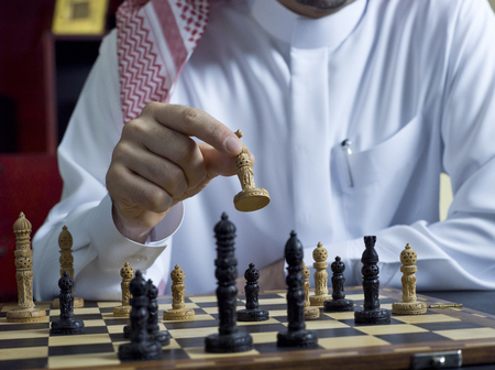Photo pour An Arab man playing chess at his desk - image libre de droit