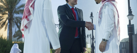 Photo pour Middle eastern and caucasian businessmen shaking hands outdoor on a sunny day - image libre de droit