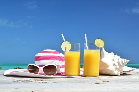 Orange juice, hat, sunglasses and conch on the tropical beach. Exuma, Bahamas
