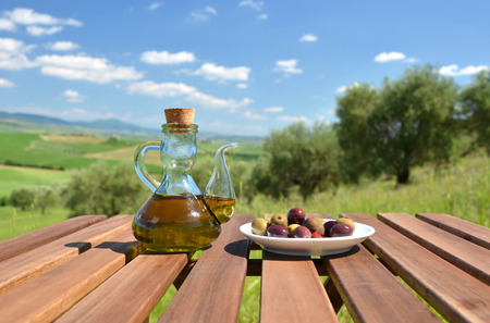 Olive oil and bread on the table against Tuscan landscape. Italy