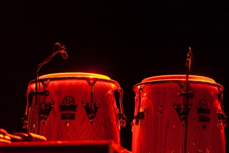 Steel drums illuminated on a stage during an orchestral performance at the Buena Vista Social Club