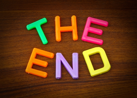 The end in colorful toy letters on wood background