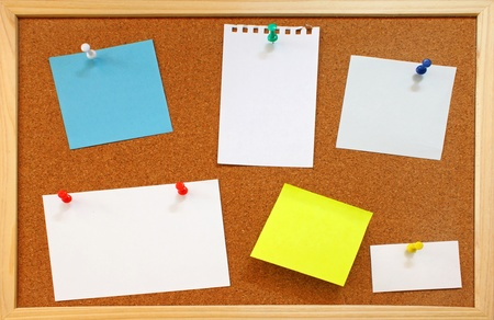 Blank notes with colorful push pins on framed cork board