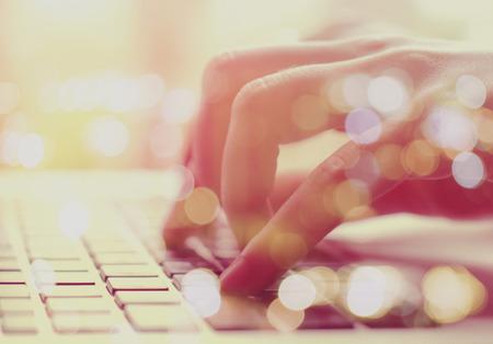 Photo pour Double exposure of female hands typing on laptop with bokeh light - image libre de droit