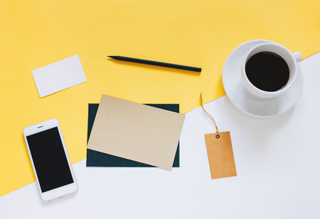Creative flat lay photo of workspace desk with smartphone, coffee, tag and letter with copy space background, minimal styled