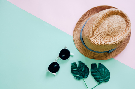 Flat lay of minimal accessories items for summer with hat and sunglasses on colorful background