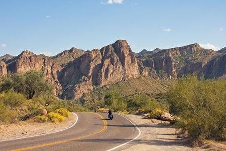 Motorcycle riding through Arizona desert landscape with jagged mountains ahead