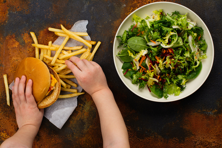 Child making choice between healthy salad and fast food. Choosing unhealthy burger instead of fresh salad. Diet or healthy lifestyle concept