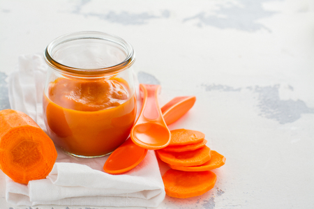 Homemade carrot puree with ingredients on white background. Space for text