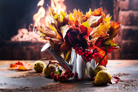 Watering can with autumn leaves and ripe pears near fireplace. Thanksgiving day or fall concept. Copy space