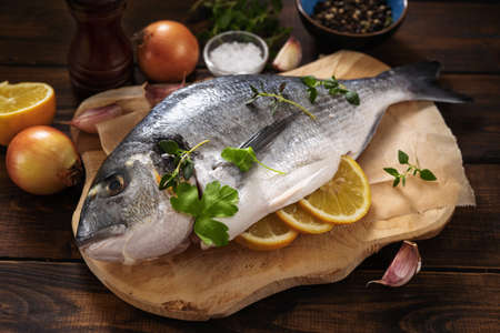 Photo pour Fresh raw fish on wooden board with ingredients - image libre de droit