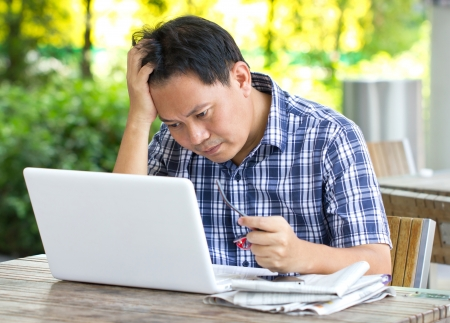 Stress Asian man looking at laptop