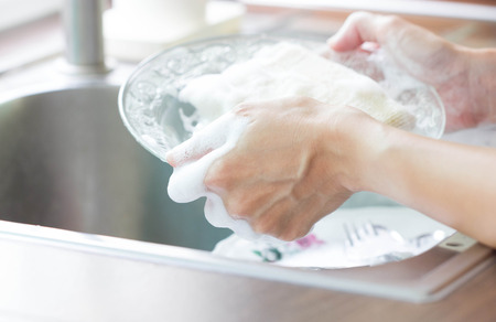 Photo pour Close Up Woman Hand Holding Yellow Sponge And Washing Saucer With Washed Dishes - image libre de droit