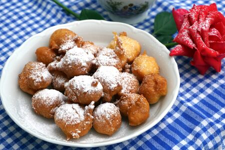 Photo for Sweet homemade fritter balls powdered with icing sugar and served on decorated table - Royalty Free Image
