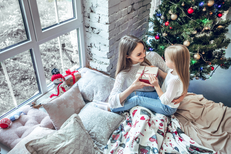 Foto de Girl holding gift box smiling and sending present to mom. Happy child girl near a Christmas tree with Christmas present bought from shopping sale. xmas holiday sending gift. top view - Imagen libre de derechos