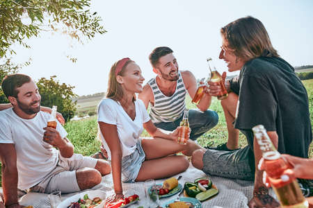 Photo for Group of teenagers having a picnic on the park. Young friends sitting together with beers in park. Young friends enjoying picnic - Royalty Free Image