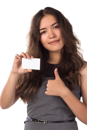 Photo for Young smiling asian woman holding a blank card, shows thumbs up gesture isolated on white - Royalty Free Image