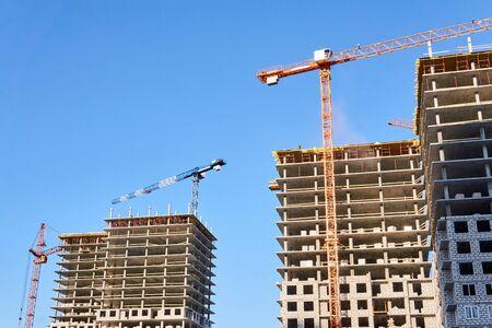 Photo pour two multistory blocks of flats under construction with tower cranes against the sky - image libre de droit