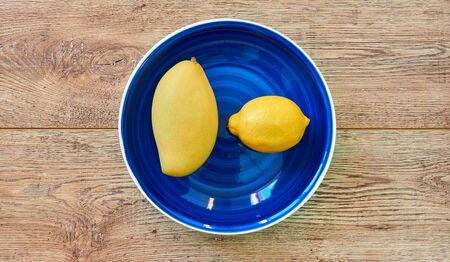 Photo pour yellow fruits - lemon and mango - on a blue plate on a wooden tabletop - image libre de droit