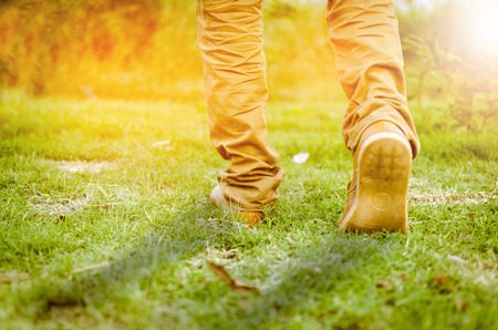 Photo pour a walk towards brighter future, a beautiful shot of feet walking towards sunlight or going ahead towads sunrise or sunset on the grass or park or field running or morning walk or workout, tone added  - image libre de droit