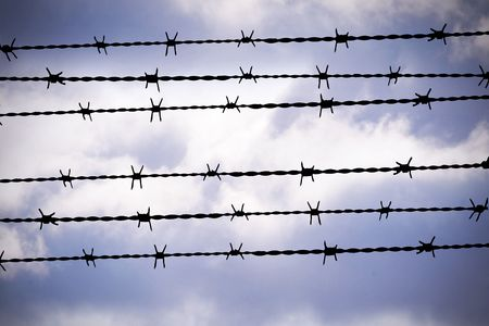 people are captured behind barbed wire