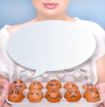 Portrait of young pretty business woman against grey background holding eggs with different emotions on their rawn faces. People management conceptual photo.