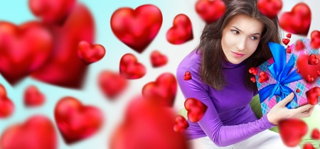 Delighted woman opening a gift sitting on the bean bag at home and beautiful red heart shapes are flying around. Valentine`s day concept poster
