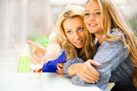 Two beautiful women drinking coffee and chatting at mall cafe. One of them pointing to copyspace and they both looking there.