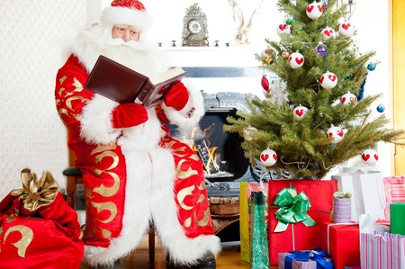 Santa sitting at the Christmas tree, fireplace and reading a book