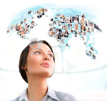 Foto de Young successful woman looking at world map with profile photos of her colleagues - Imagen libre de derechos
