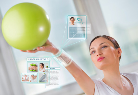 Photo pour Woman doing exercise with ball wearing smart wearable device with futuristic interface - image libre de droit