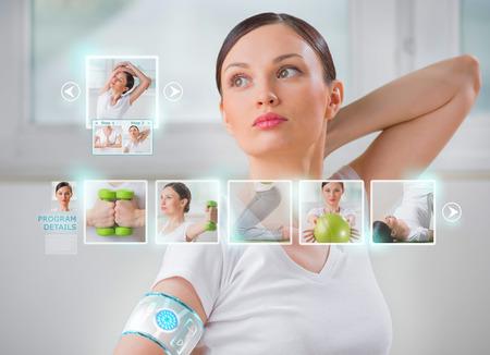 Photo pour Woman doing exercise wearing smart wearable device with futuristic interface  - image libre de droit