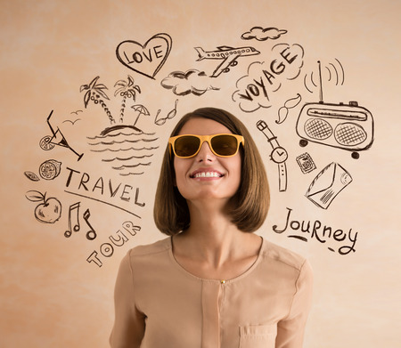 Positive smiling woman wearing sunglasses planning her vacation. Sketches of her plans of trip around her