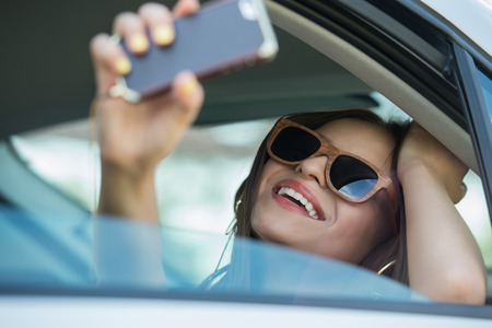 Holidays and tourism concept - smiling teenage girl taking selfie picture with smartphone camera outdoors in car