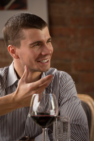 Man having fun at restaurant while drinking red wine and chatting with friends