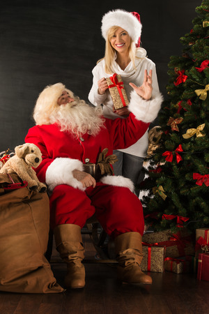 Photo of Santa Claus with his wife surprising and opening Christmas gift at home
