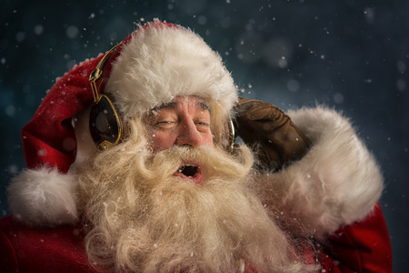 Santa Claus is listening to music in headphones wearing sunglasses. Christmas.