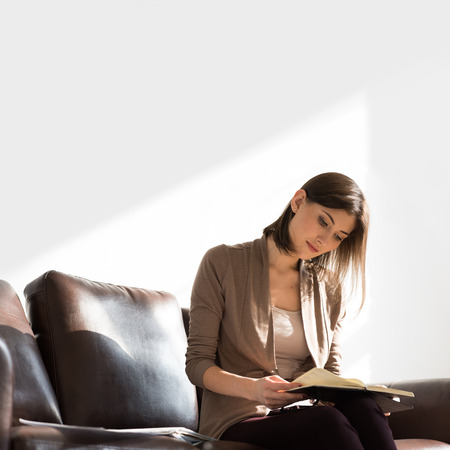 Portrait of pensive thinking business woman holding notepad or organizer and planning at her office