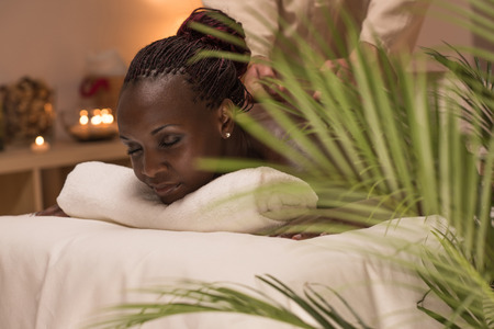 Masseur doing massage to african woman body in the spa salon. Beauty treatment concept.