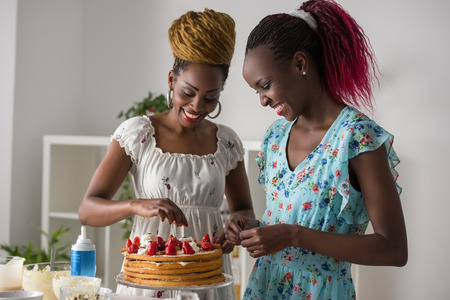 Young african women at the kitchen cooking cake with strawberry