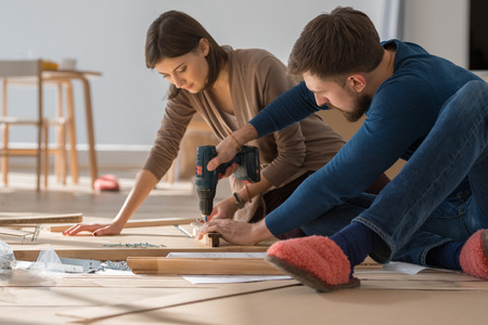 Photo pour Happy young couple putting together self assembly furniture as they move into their new house. - image libre de droit