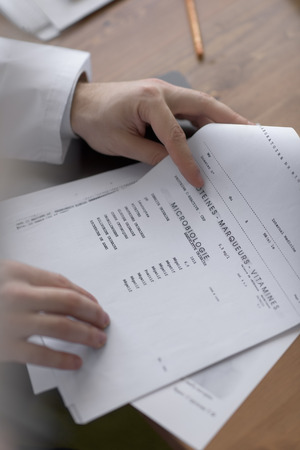 Doctor working with test results of his patient at office