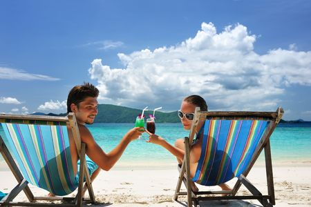 Photo for Couple on a tropical beach in chaise lounge - Royalty Free Image