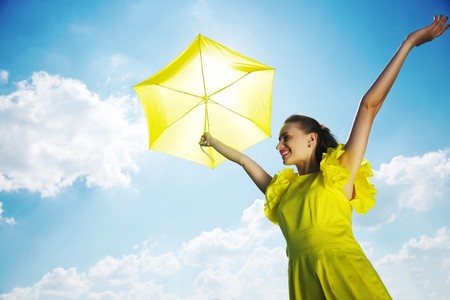 Woman holding umbrella against sun and sky