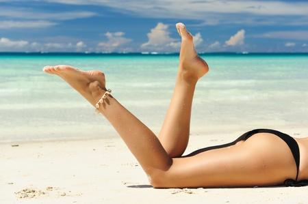 Women's beautiful legs on the beach