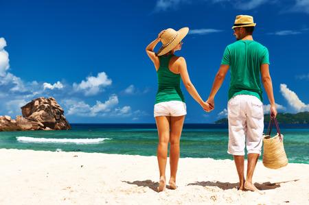Foto de Couple relaxing on a tropical beach at Seychelles, La Digue. - Imagen libre de derechos