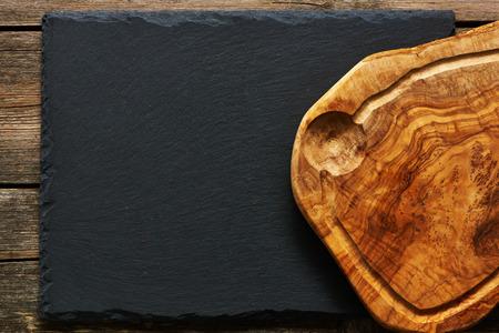 Olive wood cutting board over slate